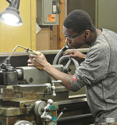 young man working with manufacturing equipment