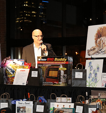 a man speaking during an event with auction items